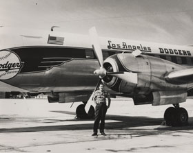 """Capt. Bump Holman shows off the Los Angeles Dodgers Convair 440 Metropolitan airplane in October 1957, just after the name was changed to reflect the club's new home city. He had it painted in Vero Beach, Florida before piloting team executives and select players on their inaugural flight to Los Angeles on October 23, 1957. In 1959 alone, Holman made 295 flights in the Convair in which he transported the Dodgers and three of the minor league teams to their road trip destinations. Dodger President Walter O'Malley once said that """"owning their own plane helped the Dodgers to win the 1959 pennant."""""""