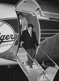 """Dodger President Walter O'Malley makes an historic journey down the steps of the Convair 440 Metropolitan twin-engine plane on the evening of October 23, 1957 at Los Angeles International Airport. He is now President of the """"Los Angeles"""" Dodgers."""