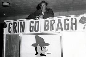 "Walter O'Malley stands above the ""Erin Go Bragh"" sign, part of the elaborate decorations at St. Patrick's Day celebrations at Dodgertown."