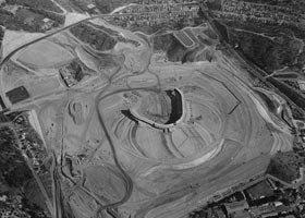 An aerial view of Dodger Stadium during the construction in 1961. The main section of the stadium is completed as the left and right wings of the stadium are visible in the center of the photo. The left and right field pavilions and parking lot are among the last items to be completed within the main portion of the stadium.