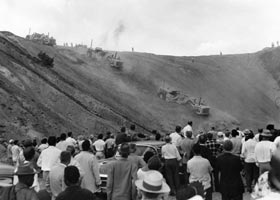 Bulldozers come over the crest of a hill as a crowd of Dodger fans view their arrival on the day of groundbreaking for the new Dodger Stadium in Los Angeles on September 17, 1959.
