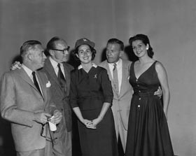 Roz Wyman shares a happy time amongst renowned movie producer Mervyn LeRoy (left), entertainers Jack Benny and George Burns and actress Pat Mowry at the June 1, 1958 Dodgerthon produced by KTTV Channel 11 in Los Angeles.