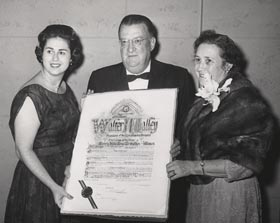"Roz Wyman presents a proclamation to Kay and Walter O'Malley on the occasion of Walter being named ""Man of the Year"" by the Beverly Hills B'nai B'rith, a Jewish fraternal and charitable organization. O'Malley was officially feted on January 28, 1962 in front of a crowd of 1,300 well-wishers by an all-star cast of celebrities."