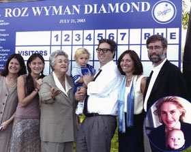 "The baseball diamond at Cheviot Hills in Los Angeles is appropriately named ""Roz Wyman Diamond"" on July 21, 2003 in recognition of her enormous contributions to the City of Los Angeles in many areas, including city government, sports, music and the arts while serving on the City Council for 12 years (1953-65). Here, third from the left, Wyman is joined by her family members (L-R): Dr. Betty Wyman, Samantha Wyman, Eugene Wyman (baby), Brad Wyman, Dr. Peggy Giffin Wyman, Robert Wyman. Inset shot of Solome Wyman with Oliver Wyman."