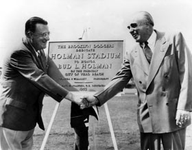 "Walter O'Malley and Bud Holman shake hands at the dedication ceremonies for Holman Stadium on March 11, 1953. Though he became a rabid Dodger fan, initially Holman knew little about baseball. As an astute businessman, he saw and acted on the opportunity to bring the Dodgers to Vero Beach for spring training. The plaque presented by the Dodgers reads, ""The Brooklyn Dodgers Dedicate Holman Stadium to Honor Bud L. Holman of the Friendly City of Vero Beach, Walter F. O'Malley, President, Emil H. Praeger, C.E., Designer, 1953."""