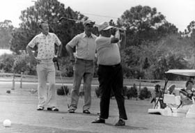 Walter O'Malley takes a swing on the Dodger Pines Country Club course as Manager Walter Alston stands behind him with an unidentified man.