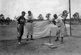 Dodger hitting instructor George Sisler (l-r), Duke Snider and Pete Reiser are practicing at the batting tee.