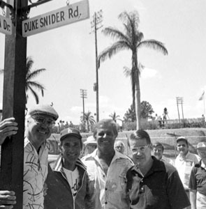 "Legendary Duke Snider stands at his street sign on the day of its dedication in 1980. ""Duke Snider Road"" was named in his honor at Dodgertown, as fellow teammates (l-r) Sandy Koufax and Don Drysdale, along with Dodger President Peter O'Malley, join the celebration."