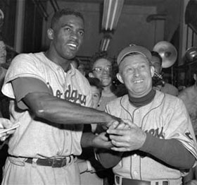 Dodger second baseman Jackie Robinson, left, slammed an upper deck home run in the 14th inning to beat the Philadelphia Phillies, 9-8, at Shibe Park in Philadelphia, September 30, 1951 and receives congratulations from Manager Charlie Dressen. With the season on the line, the Dodgers' dramatic comeback included a spectacular diving catch by Robinson in the 12th inning and his game-winning homer in the 14th  inning. Along with Don Newcombe's stellar pitching performance to keep them in the game, the Dodger win put them into a three-game National League playoff with the New York Giants for the pennant.