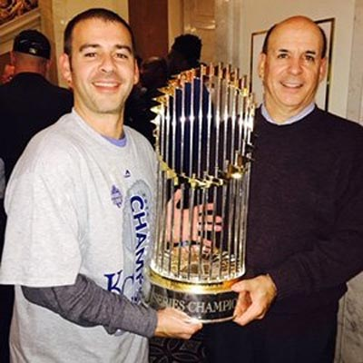 Dean Taylor and his son, Colby, pose with the 2015 World Series trophy after the Kansas City Royals defeated the New York Mets. A 1975 graduate of OHIO's Sports Administration Program, Dean Taylor created the Walter O'Malley Scholarship Fund in honor of the program's visionary.<br /><br />Photo courtesy of Dean Taylor