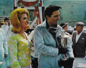 "Elvis Presley proudly displays the first-place trophy he receives for winning the ""Santa Fe Road Race"" in the 1966 movie ""Spinout"", which was filmed in part in the Dodger Stadium Parking Lot. The green hillside behind Parking Lot 38 is visible in the background."