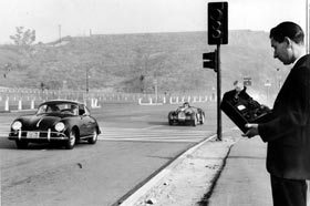 Robert E. Egan, Senior Investigator for the City's Department of Building and Safety checks noise levels of the sports cars in the parking lot at Dodger Stadium. The Dodgers received permission to hold the March 2-3, 1963 Sports Car Road Races at Dodger Stadium.