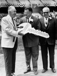 Walter O'Malley is flanked by Baseball Commissioner Ford Frick (left) and National League President Warren Giles. A giant key to Dodger Stadium is displayed at the Grand Opening ceremonies on April 9, 1962.